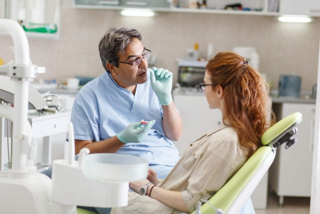 male dentist in dental office talking with female patient and preparing for treatment services idental group