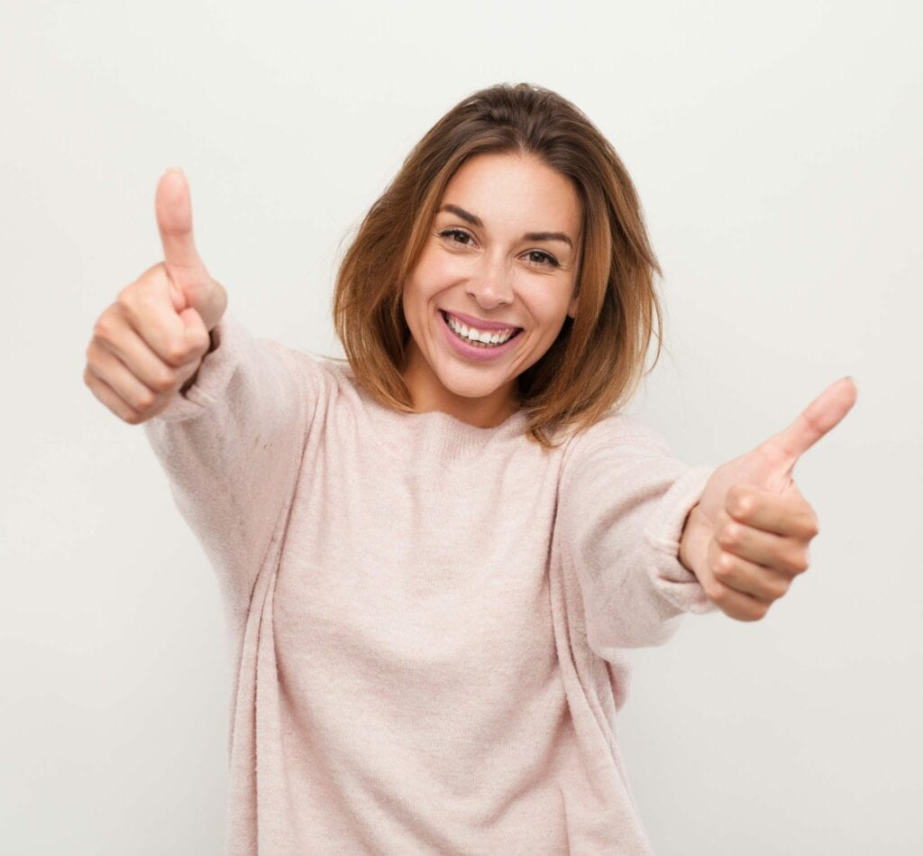 Cheerful woman gesturing thumbs up finance idental group