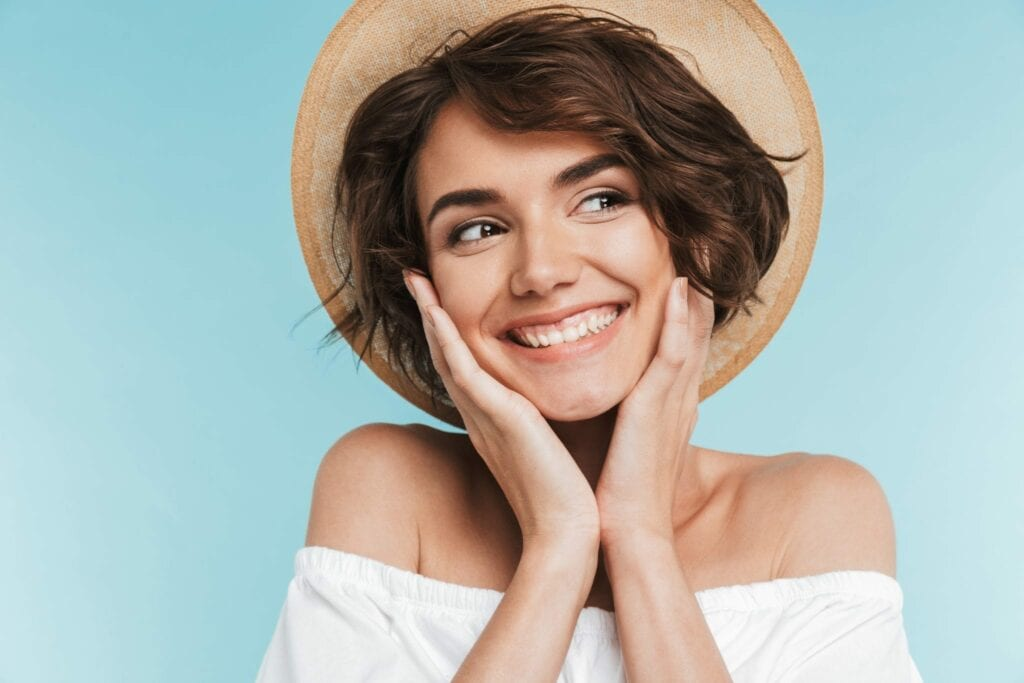 Close up of a smiling young woman in summer hat services idental group