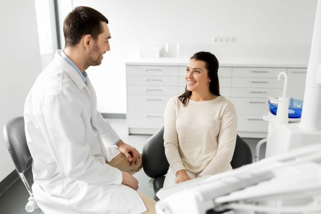 dentist talking to female patient at dental clinic services idental group