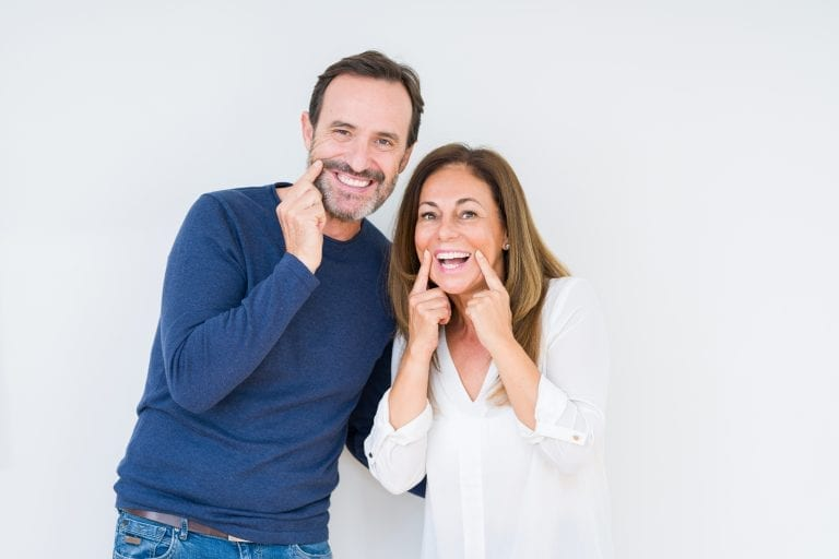 couple pointing at smile over isolated background Smiling with open mouth, fingers pointing and forcing cheerful smile dental implants services idental group