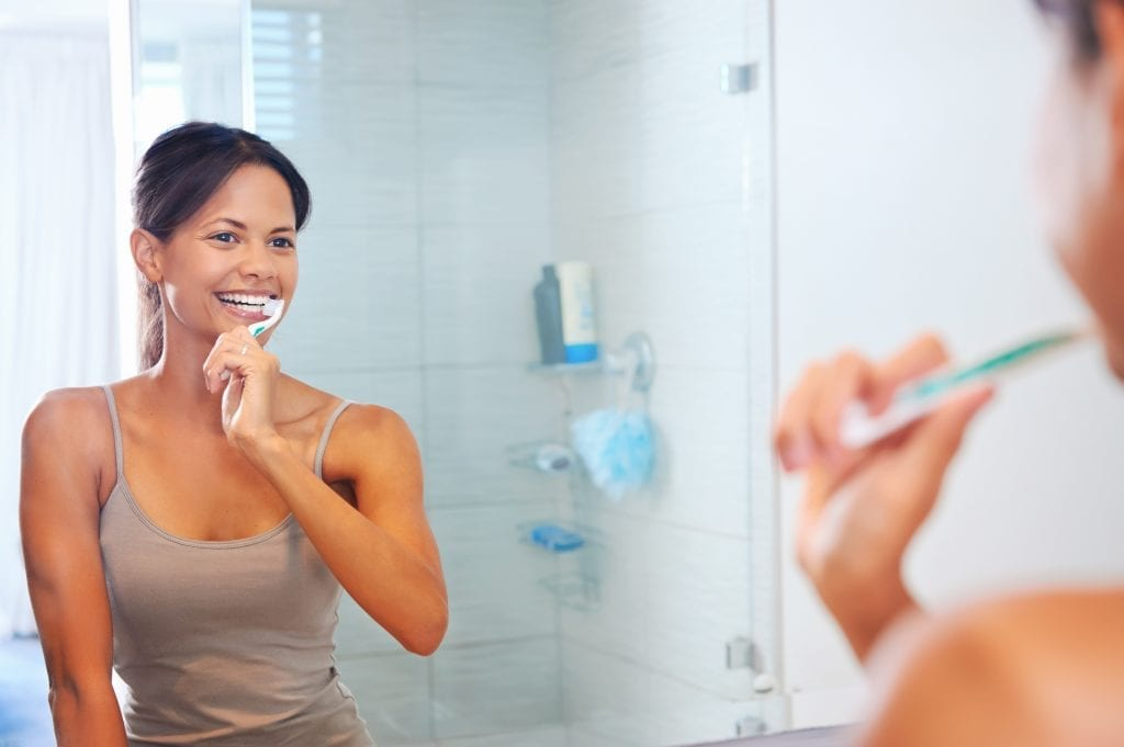 woman brushing teeth services idental group