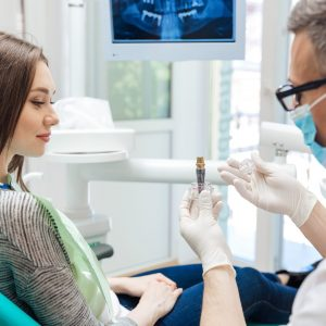 Male dentist showing his female patient a dental implant in clinic