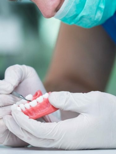 Dental prosthesis, dentures, prosthetics work. Prosthetics hands while working on the denture, false teeth, a study and a table with dental tools. home idental group