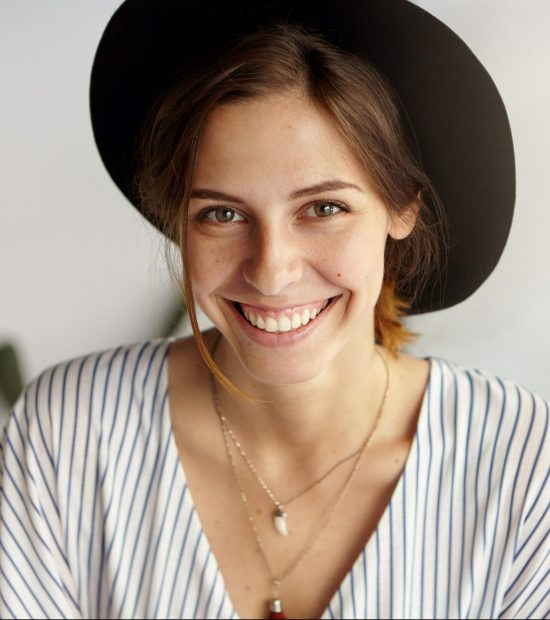 Waist up portrait of beautiful European female with dark eyes, warm smile and dark hair wearing black hat and blouse posing in camera having good mood. Smiling elegant young attractive woman in hat