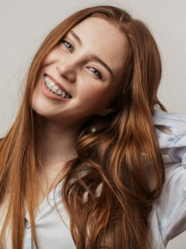 Happy young red-haired woman in braces smiling on white background services idental group